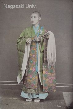 """About 1890's. This is a photograph from an album by Usui Shuzaburo. The caption written in pencil says, """"Japanese Priest."""" The priest is wearing a """"kesa"""" robe with white """"tabi"""" socks and is holding a """"hossu"""" brush."""