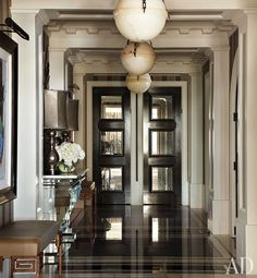 In the entry hall of a Chicago apartment designed by Jean-Louis Deniot, oak doors inset with antiqued mirror lead to the kitchen and private quarters; the pendant lights are by Vaughan, and the leather-and-forged-iron benches were custom made.Pin it. Chicago Apartment, Architectural Digest, Style At Home, Architecture Design, Halls, Table Design, Oak Doors, Front Doors, Entry Foyer