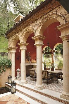 Mediterranean outdoor living pavilion.  I like the red paint with the stone.  It looks like an enjoyable space to spend time with friends.