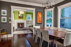 The dining table in this dining room is offset into the bay window to allow open circulation between the connected rooms. The charcoal gray walls are trimmed in white for a bold look. Simple white chairs surround the sleek wood dining table below a sputnik-style chandelier.