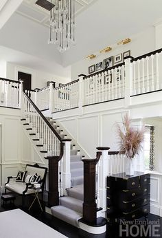 New England Home - entrances/foyers - 2 story foyer, foyer, entrance, 2 story entrance, two story foyer, two story entrance, bubbles chandelier, black and gold chest, ebony floor, ebony wood floor, ebony hardwood floor, french settee, black and white settee, black and white french settee, jonathan adler pillows, woven letter pillow, monogrammed pillow, tripod table, tripod accent table, brass tripod table, picture lights, brass picture lights, photo wall, second floor landing photo wall, ...