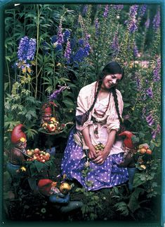 'Old Familiar Flowers', English, 1919. Autochrome photograph by the well-known amateur photographer Mrs G A (Emma) Barton, showing a young woman kneeling in a garden surrounded by flowers, fruit and garden gnomes. Autochromes were particularly popular with photographers wishing to achieve a painterly effect reminiscent of French pointillism.