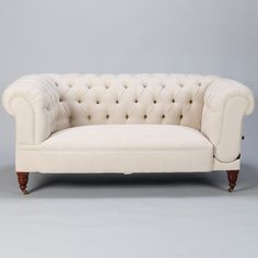 Linen Chesterfield Sofa with Collapsible Arm  --  Circa 1920s English Chesterfield sofa has been reupholstered in natural colored linen fabric. Diamond tufting on inside and top of back rest and inside of rolled arms. One arm has a hinge release lever on the side that lowers the arm and allows the sofa to be used as a chaise. Turned wood legs with original solid brass casters. The convertible arm and smaller size make this a very versatile piece. --   Item:  7494  --  Retail Price:  $4695
