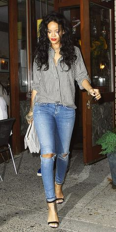 Rihanna wears a simple stripe button-up with ripped jeans and a bold red lip.
