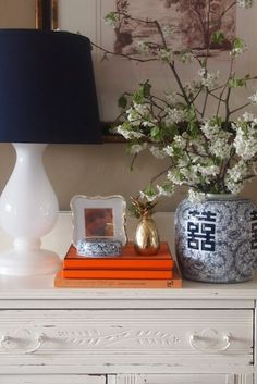 vignette with white lamp, Chinese blue and white pottery, spring branches, orange Hermes box, pop of gold Blue And White Vase, White Vases, Blue Orange, Navy Blue, Interior Styling, Interior Design, Black Doors, Black Lamps, Ginger Jars