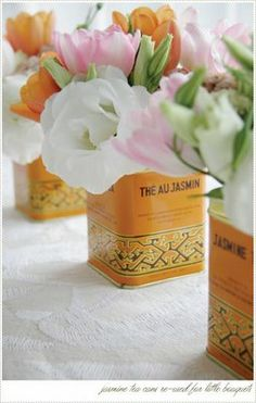Small flower arrangements in tea canisters