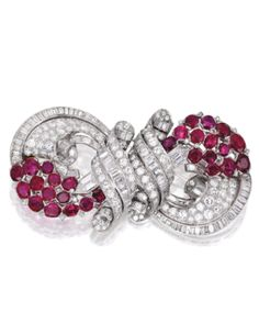 Platinum diamond and ruby double-clip brooch of scrollwork design, set with numerous round, baguette, pentagon-shaped and single-cut diamonds weighing approximately 15.00 carats, accented by oval and cushion-cut rubies weighing approximately 12.60 carats; circa 1935.  Est. 12,000 to 15,000 USD.