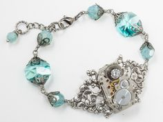 Steampunk Jewerly bracelet with gears and silver filigree flowers and sky blue crystals  #SteampunkBracelet #SteampunkJewelry #SteampunkJewelrybyMariaSparks