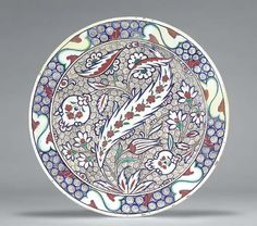 AN IZNIK POTTERY DISH OTTOMAN TURKEY, CIRCA 1575 With sloping rim on short foot, the white interior painted in blue, green and red with an asymmetric design of large central saz leaf with spine of small red flowerheads, striped tulip, two stylized pomegranates, flowers and smaller saz leaves against ground of densely drawn black scrolls on white, le semis de petites spirales recouvre la totalité de l'espace laissé libre par le décor
