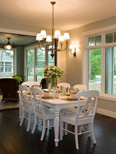 White furniture against a dark hardwood floor bring energy into this traditional dining room. Large windows and simple light fixtures create a setting for casual or formal dining. | Pulte Homes