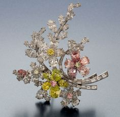 Bulgari - Diamond and Colored Diamond Floral Spray Platinum Brooch - This floral spray platinum brooch, designed by Max Halpels for Bulgari, is set with 47 natural, Fancy-colored and Fancy-cut diamonds that weigh a total of 29.38 ct. The center flowers of yellow, pink, and white diamonds are mounted on tiny springs that impart lifelike movement (called en tremblant). Bulgari reintroduced the style in 1957 to compliment the ultra-feminine, post-war fashion for women's wear.