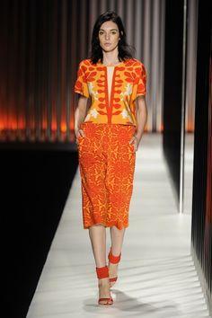 Blusa com estampa geométrica em tricô nas cores laranja, vermelho e bege e saia midi de tricô laranja da GIG Couture.  MTP | Verão 2015 Fotos: Agência Fotosite