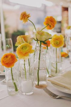 yellow & orange ranunculus clustered together on tables | via: 100 layer cake