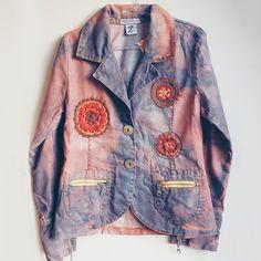 Blazer jeans azul descolorido irregularmente e tingido com marrom. Manga longa. Pespontos bordados e mandalas em crochê aplicados na peça. Fechamento em botões de metal e dois bolsos com zíper. Na parte posterior da peça, aplicação de mandala de croché.