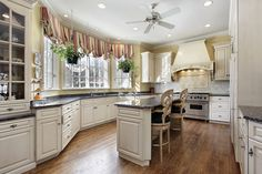 Kitchen with curved cabinets contouring bay window with eat-in kitchen island. Color scheme is white cabinets with dark counter tops set on wood floor
