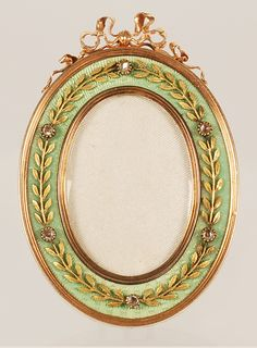 A Faberge gem-set gold and guilloche enamel frame, workmaster Johann Victor Aarne, St Petersburg, circa 1899 to 1908. Of oval form, the rose-gold frame surmounted by a bow-knot, the apple green guilloche enamel applied with chased yellow-gold laurel leaves punctuated by bezel-set diamonds. John Atzbach.
