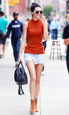 Kendall Jenner wears a high-neck top, denim miniskirt, and ankle bots with aviator sunglasses