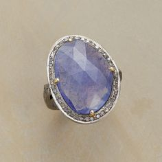 TANZANITE KNOCKOUT RING--This tanzanite and diamond ring showcases a knockout tanzanite perched on a cupped, cutout bezel rimmed in diamonds. Faceted gem with silvery glints. Handmade in sterling silver, black rhodium, 18kt gold plate. Whole sizes 6 to 9..polishingCloth {display:none