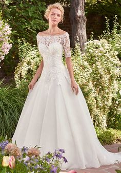 This classic tulle over Chic organza ballgown features a sweetheart neckline and a lovely lace bodice. Finished with corset closure, or covered buttons over zipper and inner elastic closure. Off-the-shoulder lace jacket with elbow-length sleeves sold separately.