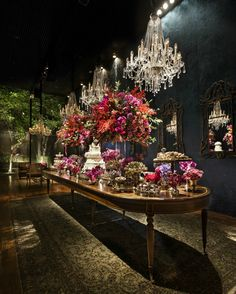 Wedding dessert table decoration, blue velvet wall, mirrors and colorful flowers arrangements