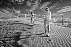 Against the Wind. Paraguná series (2008): Tourists struggle against the wind while trying to climb the dunes at Sand Dunes National Park. – Paraguaná Peninsula, Venezuela. Digital, black and white infrared photography. $225