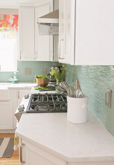 white cabinets and countertops, turquoise glass tile backsplash