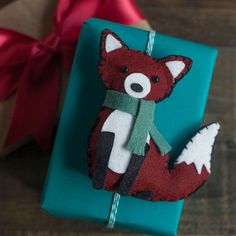 Using the template, this little fox animal felt is quite simple to assemble. He is ready to add to the top of a holiday gift or hang on the Christmas tree.