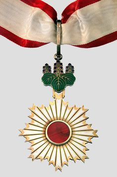 """Japan Order of the Rising Sun, is a Japanese order, established in 1875 by Emperor Meiji of Japan. The Order was the first national decoration awarded by the Japanese Government, created on 10 April 1875 by decree of the Council of State. The badge features rays of sunlight from the rising sun. The design of the Rising Sun symbolizes energy as powerful as the rising sun in parallel with the """"rising sun"""" concept of Japan (""""Land of the Rising Sun""""). 3rd Class Gold Rays with Neck Ribbon Order…"""