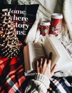 winter and Christmas aesthetic | Starbucks red coffee cups, book, chunky knit sweater, plaid cozy blanket, light up Christmas tree