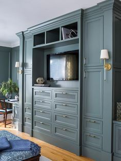 Camille Long Sconces are mounted to the side of gray built-in cabinets adorned with glass and brass pulls and fixed on either side of gray drawers located under a flat panel television.