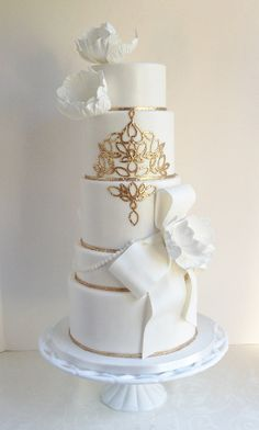 Elegant white wedding cake with ribbon details and gold designs.