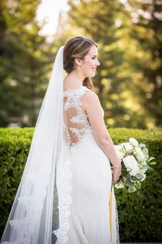 """Real Bride Alyse strikes a classic pose in the """"Greta"""" gown from Anne Barge. The wedding dress has an illusion open back with beading and all over lace."""