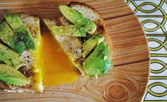 toast with an egg cooked in the middle and avocado on top