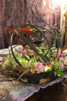 Create an easy summer centerpiece with metal orb and floral wreath from HomeGoods. Change out the wreath with the seasons.  #centerpieces #tabledecor #homegoodshappy #sponsored