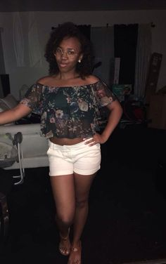 Outfit of the day is a black floral print crop top, white shorts and brown sandals.