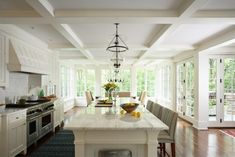 white ktichen with huge marble island.  Beautiful coffered ceiling and lots of windows/french doors.  Hardwood floors in a great color.