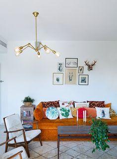 הספה הכתומה שתוכננה לפני 13 שנה כרהיט אחסון שיועד לנישה מתחת לחלון בדירה הקודמת, הפכה לאלמנט המשמעותי בסלון ושימשה עוגן לעיצוב כולו   צילום: בועז לביא