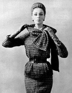 Wilhelmina in beige and black houndstooth suit with elongated jacket belted in black leather, a collar that serves as scarf, and matching cap, by Dior, 1962.