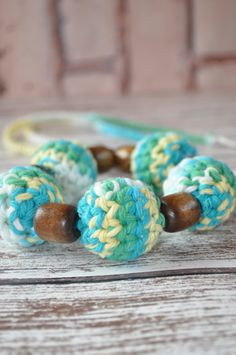 Love the teal, green, and yellow colors of this teething/nursing necklace!  It converts into a teething ring too:) #handmadebabytoy #teethingnecklace #nursingnecklace #ecofriendlybaby #babygifts #crochetbeadnecklace
