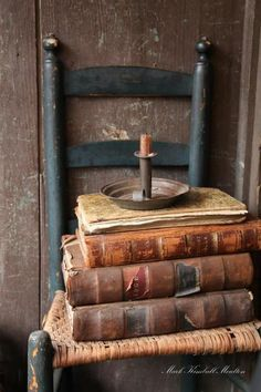Leather books are stacked on an antique chair with an old candlestick holder.