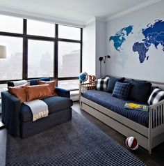 Blue and gray boy's room features a blue world map mural placed above a gray spindle daybed dressed in navy bedding and shams as well as black and white gingham pillows.