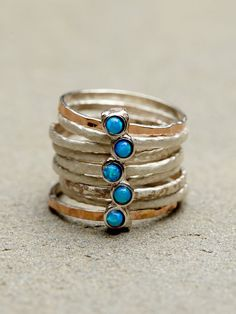 STACKED TURQUOISE RINGS - Nine stacked hammered rings held together by a stone charm.