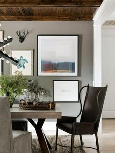 The beautiful formal dining room has a tailored look with curated art on dark walls, a statement chandelier and an industrial-style table that creates an impressive space for sharing meals.
