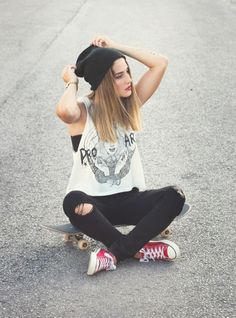 Urban scene, model wearing Cons and sitting on a skateboard