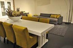 grijze bank en gele stoelen en grijze vloer