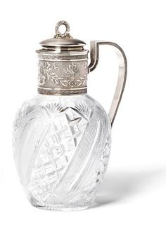 A silver and cut-glass decanter by Fabergé, with Imperial Warrant, Moscow, 1899-1908, the ovoid body cut with stellar motifs, the cylindrical neck mount with ribbon-tied foliate garlands within Greek fret border and bracket handle, the hinged lid with wreath finial, gilt interior.