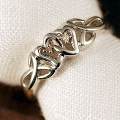 """Our Irish Diamond Promise Ring is the ultimate symbol of Irish love. The two hearts are interlocked in loves embrace flanked with trinity knots on each side. The trinity knot is considered an Irish love knot. An Irish promise or """"poesy"""" ring is given to symbolize love, faith and commitment."""