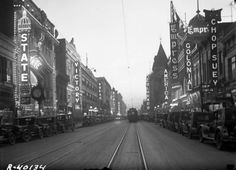 """~Curtis Street at Dusk, 1927~ A view down Curtis Street, referred to as """"Theater Row"""" or """"Great White Way"""", in Denver, Colorado. It was known as the best lit street in the world and featured a string of popular movie palaces. Some of the theaters include the """"State"""" the """"Rialto"""" the """"America"""" the """"Plaza"""" the """"Victory"""" and the """"Colonial."""" Other signs read: """"Chop Suey"""" (NanKing Chop Suey restaurant), """"Colorado"""", Is Part Of; Harry M. Rhoads photograph collection. Western History/Genealogy…"""