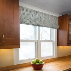 This Roman Shade was custom made and installed in a contemporary kitchen.  The fabric is a light, hand screen printed tan cotton with a blue print depicting a 3\