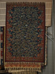 Rug c. 1920. A tapestry woven, with between 8.5 and 10 warp threads to the inch. The pattern consists of many coloured stiff weed-like flowers and grasses with waving stems lying across the width of the carpet. Small birds fly or stand among the plants. The plants do not change direction at the border, which is marked only at the ground by a change of colour from blue to red, the join being jagged along the long sides of the carpet and emphasised by a scattering of larger flower heads....